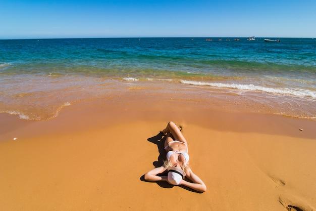 ビーチでリラックスして日光浴をしている水着ビキニの女性のトップ空中ドローンビュー