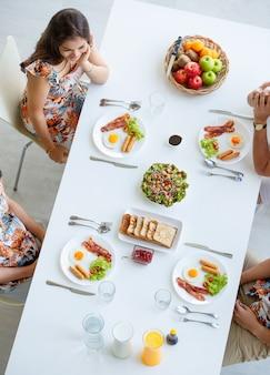 上空からの眺めアジアの4人の家族がカジュアルなカラフルなリフレッシュの服を着て、自宅の快適で清潔なダイニングルームで健康、幸福、暖かさを持って朝の朝食に一緒に座っています。