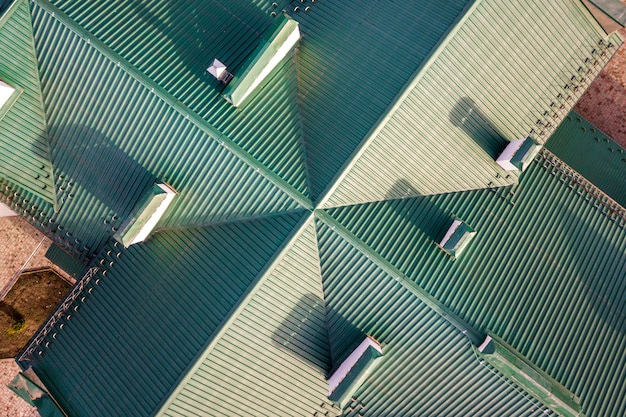 Top aerial view of building green shingle tiled roof construction.
