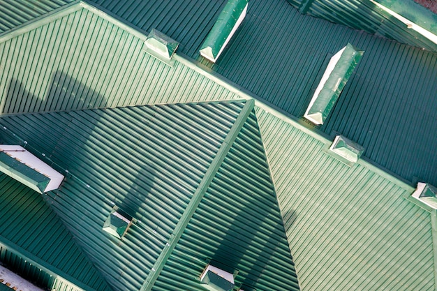 Top aerial view of building green shingle tiled roof with complex configuration construction. abstract background, geometrical pattern.
