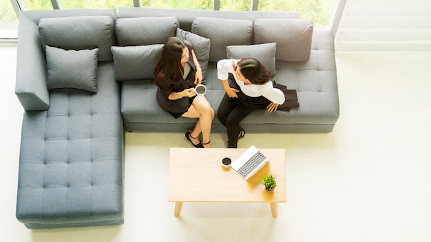 Top aerial view business woman talk and sit on grey bench sofa with black coffee drinking.