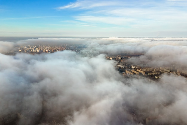 Top aerial view of fluffy white clouds over modern city with high rise buildings.