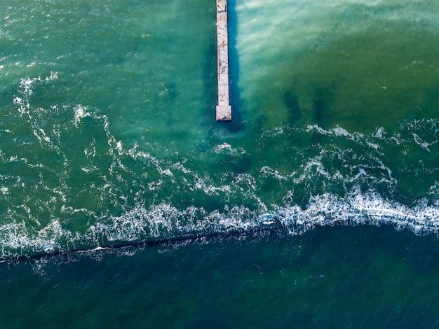Вид сверху с дрона на морской пейзаж с прозрачной бирюзовой водой, волнорез и пирс. естественный морской фон с волнами пены. место для текста.
