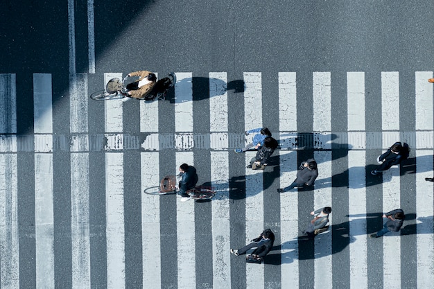 Top aerial view of men and women in winter cloth walk and ride bicycle across crosswalk in street