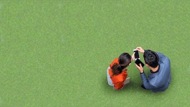 녹색 잔디에서 프리젠 테이션을 위해 스마트 폰을 사용하여 회의하고 사용하는 사업가 및 여성 사람들의 상위 공중보기
