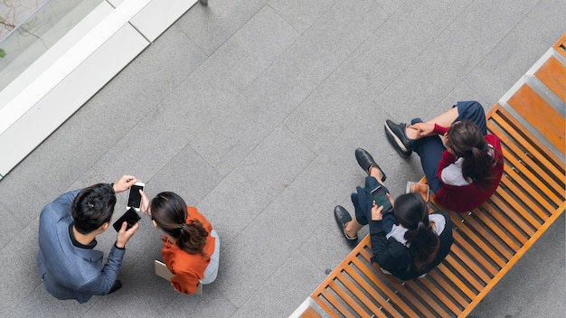 Верхний вид с воздуха на бизнесменов и женщин, встречающих людей и использующих смартфон для презентации на уличном пешеходе и двух девушках, сидящих на скамейке.