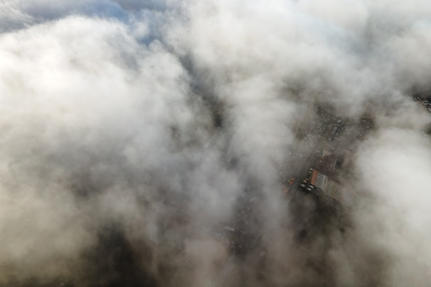고층 건물이 있는 현대적인 도시 위로 푹신한 흰 구름의 최고 공중 전망.