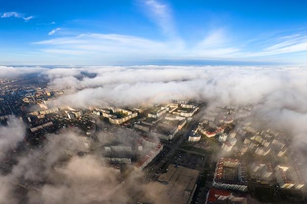高層ビルのある近代的な都市の上のふわふわの白い雲の空中写真。