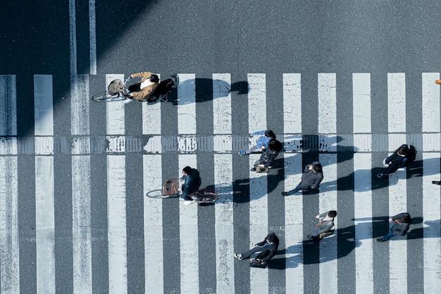 Верхний вид с воздуха на мужчин и женщин в зимней одежде, идущих и катающихся на велосипеде по пешеходному переходу на улице