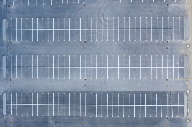 Top aerial view of parking to a large area empty asphalt car parking.