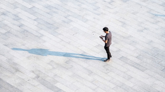 Top aerial view people walk on across pedestrian concrete with black silhouette shadow on ground