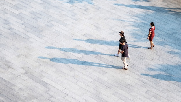 Top aerial view people walk on across pedestrian concrete with black silhouette.