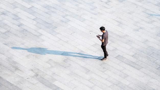 지상에 검은 실루엣 그림자가있는 보행자 콘크리트를 가로 질러 걷는 최고 공중보기 사람들