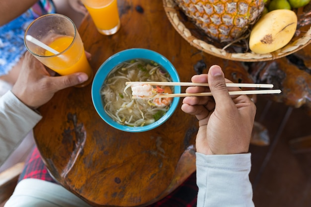 Top angle view of man eating noodles chopstick and drinking orange juice trying traditional asian fo