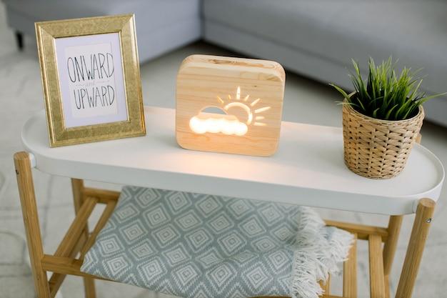사진 프레임이있는 커피 테이블, 태양과 구름 그림이있는 장식용 나무 램프 및 고리 버들 꽃 냄비에 녹색 식물의 최고 각도보기. 손으로 만든 가정 장식, 테이블 밤 램프.