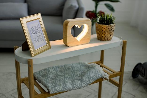 손의 최고 각도보기는 가정 장식, 사진 프레임이있는 커피 테이블, 심장 그림이있는 장식용 나무 램프 및 고리 버들 꽃 냄비에 녹색 식물을 만들었습니다.