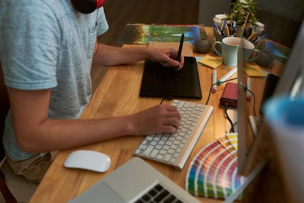 Взгляд верхнего угла мужского веб-дизайнера на работе