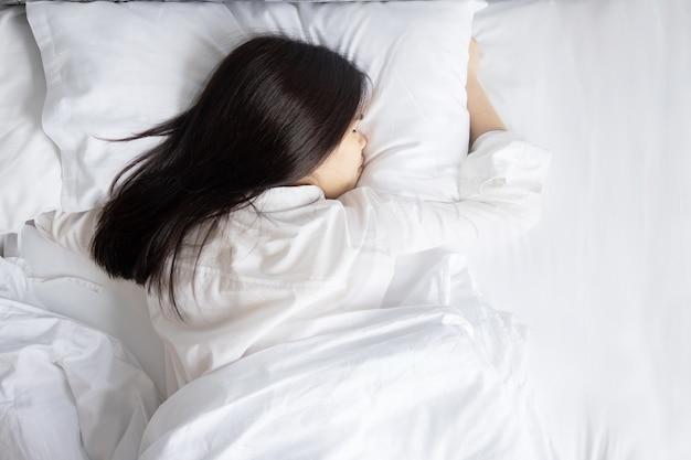 彼女のベッドで横になって寝ているアジアの女性の上面背面図