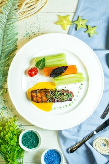 Top  baked salmon served with fresh vegetables and herbs on white plate