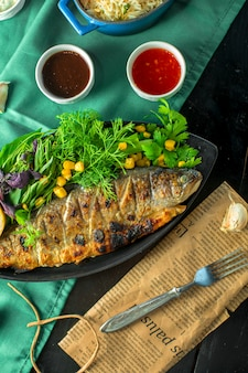 Top  baked sea bass served with fresh herbs and sauces on the table
