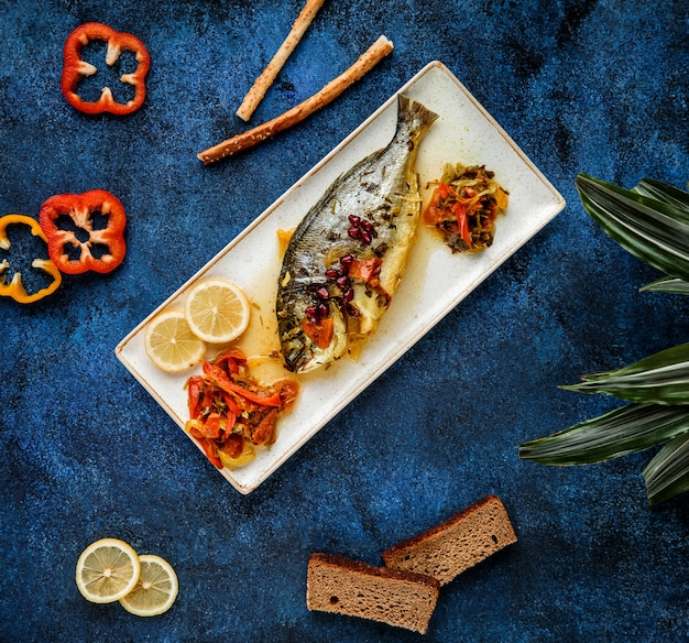 Top  baked sea bass serves with vegetables and lemon on platter on blue