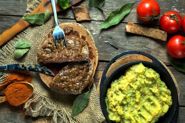 Стейк из говядины с соусом из перца на деревянной доске