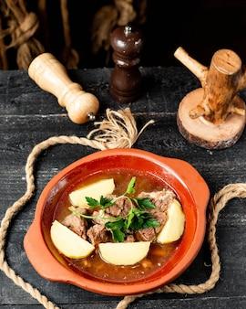 Spezzatino di manzo con patate in pentola di terracotta