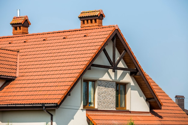 Top of big modern expensive residential house cottage with steep shingled brown roof, high brick chimneys, stucco walls, gutter system and plastic attic windows on blue sky