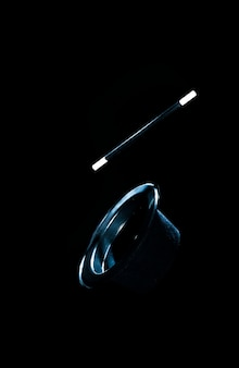 Top black hat and magic wand in air against black background
