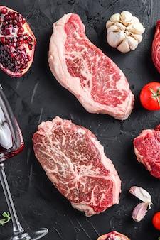Top blade, beef steak cuts, with herbs, seasoning  on black table, top view.
