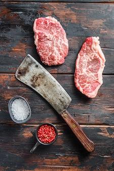 어두운 나무 소박한 테이블에 오래 된 정육점 칼 칼과 조미료와 톱 블레이드 유기농 고기 컷, 원시 대리석 쇠고기 스테이크.