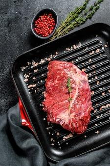 Верхний стейк на сковороде гриль, сырое мясо, мраморная говядина. черный фон. вид сверху