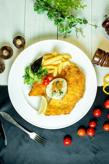 Top  breaded chicken fillet served with french fries fried egg and cherry tomatoes on plate