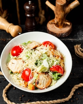 Top  caesar salad with chicken and parmesan cheese in bowl on dark