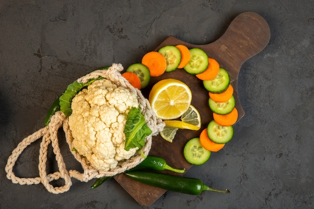 Top  carrot and cucumber slices and cauliflower on wooden cutting board on dark