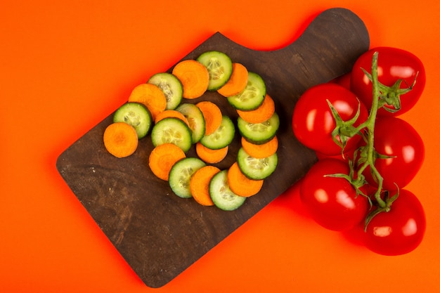 Top  carrot and cucumber slices with tomatoes on wooden cutting board on orange