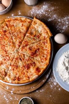 木製のテーブルでスライスしたトマトとスパイスのトップチーズピザ