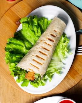 Doner di pollo superiore avvolto in lavash su lattuga sul tavolo di legno