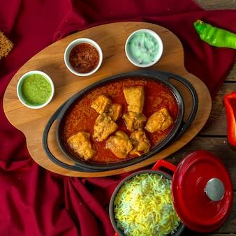 Stufato di pollo con aglio in salsa di pomodoro servito con spezie su tavola di legno