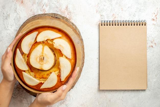 白いテーブルの上で手に木製まな板の梨ケーキの横にある上部のクローズアップ梨ケーキクリームノートブック