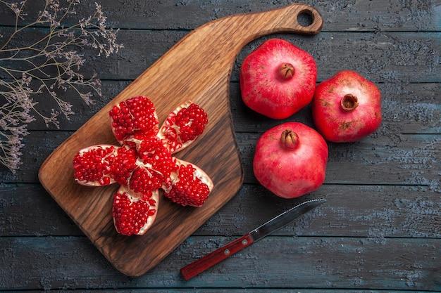 어두운 배경에 있는 세 개의 빨간 석류 칼과 나뭇가지 옆에 있는 나무 판자에 잘 익은 석류 칼 보드