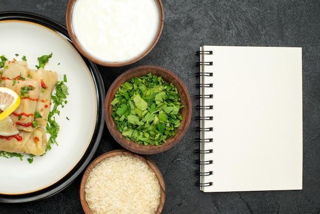 Сверху крупным планом аппетитное блюдо голубцы с лимонными травами и соусом на белой тарелке и сметанной рисовой зеленью в мисках и белый блокнот на темном столе