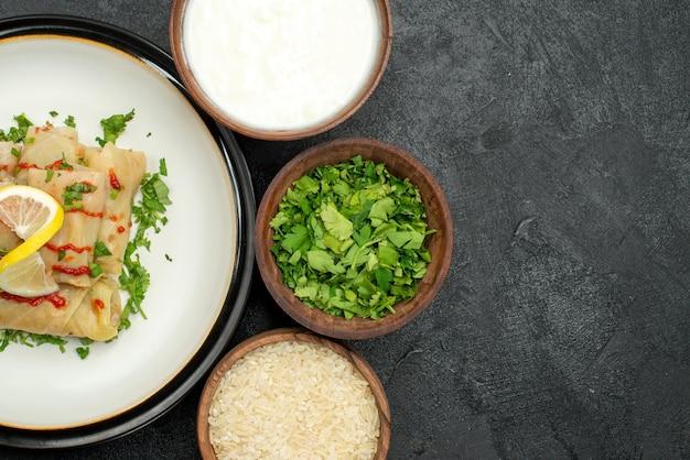 Primo piano piatto appetitoso cavolo ripieno con erbe al limone e salsa su piatto bianco ed erbe di riso con panna acida in ciotole sul lato sinistro del tavolo scuro