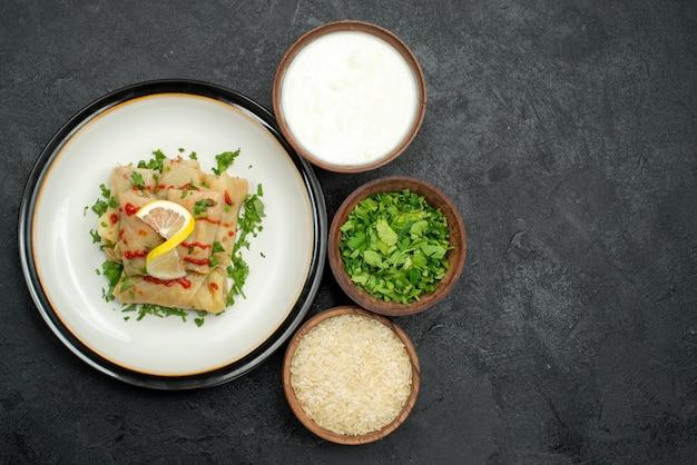 Cavolo ripieno di cibo appetitoso lato primo piano con erbe al limone e salsa su piatto bianco ed erbe di riso e panna acida in ciotole sul tavolo nero