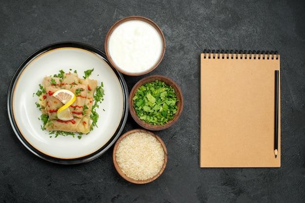 Primo piano cibo appetitoso cavolo ripieno con erbe al limone e salsa su piatto bianco ed erbe di riso e panna acida in ciotole accanto al quaderno di crema e matita sul tavolo nero