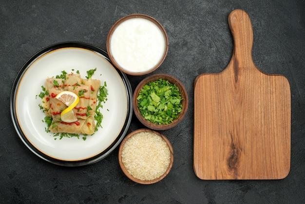 Cavolo ripieno di cibo appetitoso lato primo piano con erbe al limone e salsa su piatto bianco ed erbe di riso e panna acida in ciotole accanto al tagliere di legno marrone sul tavolo nero