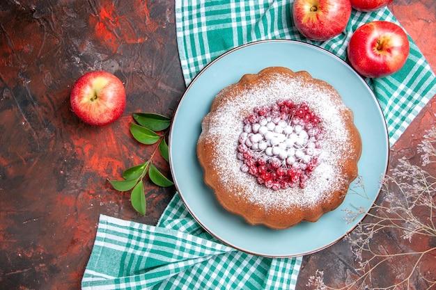 Сверху крупным планом торт торт с ягодами и яблоками сахарной пудры на бело-синей скатерти