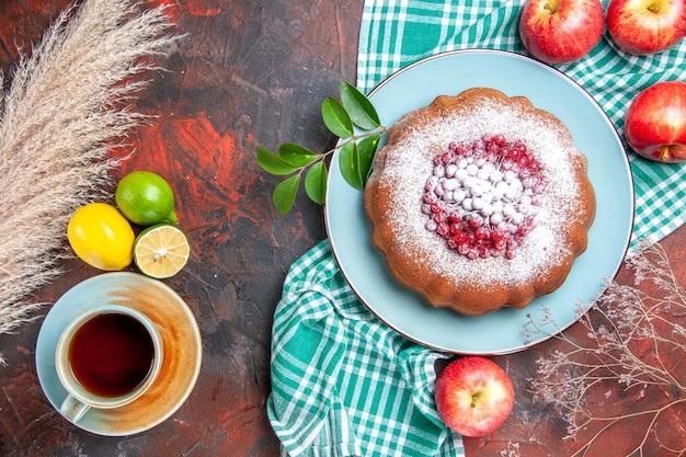 테이블보에 베리 사과가 있는 케이크 한 컵의 차 감귤류 과일을 가까이에서 볼 수 있습니다.