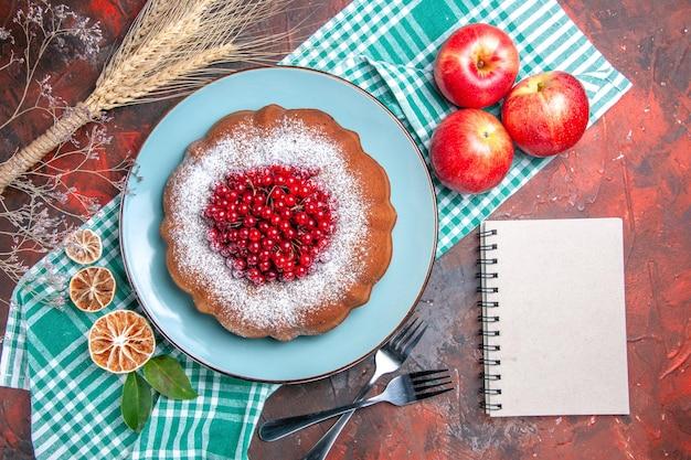 上のクローズアップビューケーキテーブルクロスフォークノートに赤スグリリンゴレモンとケーキ