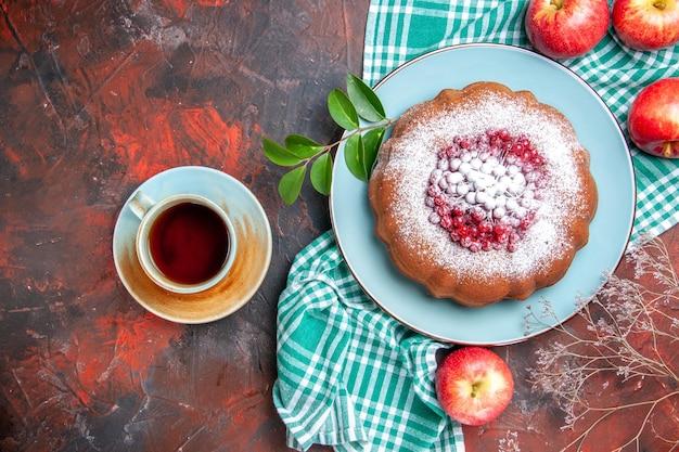 상위 클로즈업 보기 식탁보에 식욕을 돋우는 딸기 사과가 있는 케이크 케이크 한 잔